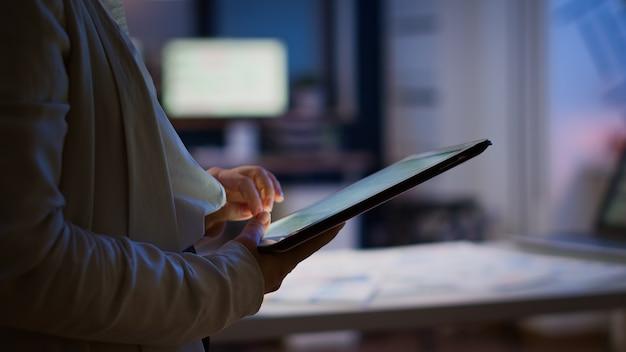 늦은 밤 비즈니스 사무실에 서 있는 휴식 시간에 여성 직원이 문자를 보내고, 메시지를 보내고, 읽습니다. 자정에 현대 기술 네트워크 무선 과로를 사용하는 사업가