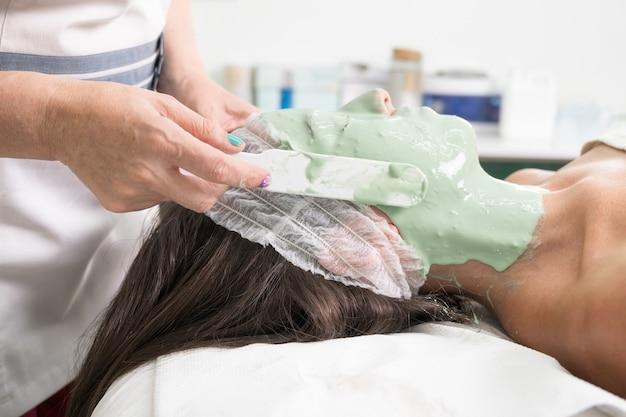 Закройте женщину, наслаждающуюся косметической маской для лица в профессиональном салоне красоты, расслабляющей процедуры в ...