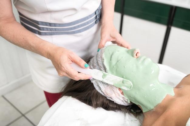Крупным планом женщины, наслаждающейся косметической маской для лица в профессиональном салоне красоты, расслабляющей процедуры в ...