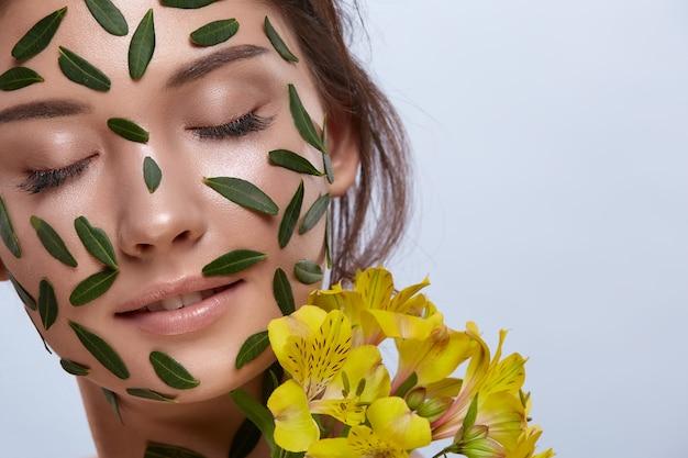 회색에 고립 된 노란색 꽃과 녹색 잎으로 가득한 여자 얼굴의 클로즈업