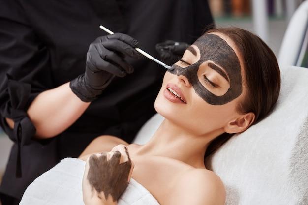 Крупным планом лицо женщины, лежащей в салоне и косметолог, применяющий угольную маску, милая женщина, имеющая процедуры по уходу за кожей в спа-салоне