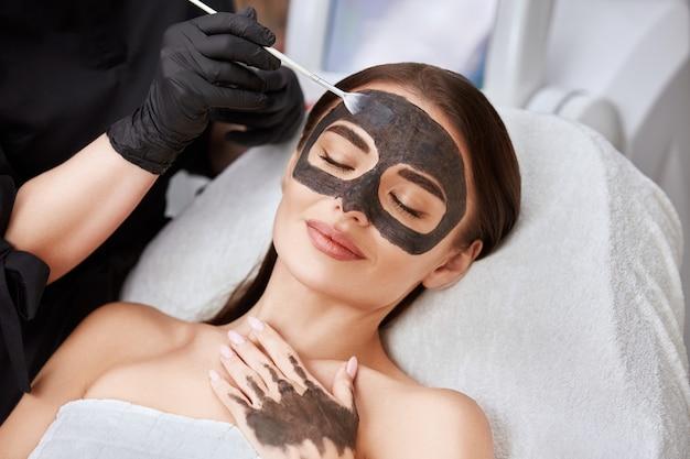 Крупным планом лицо женщины с угольной маской и рукой косметолога, наносящей ее, милая женщина, получающая уход за лицом косметолог