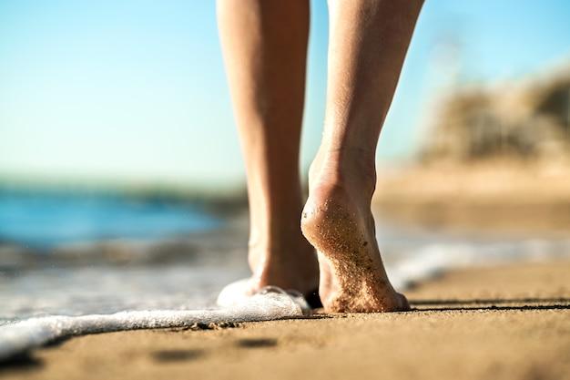 황금빛 해변에 발자국을 남기고 모래 위를 맨발로 걷는 여성의 발을 닫습니다. 휴가, 여행 및 자유 개념입니다. 여름에 휴식을 취하는 사람들.