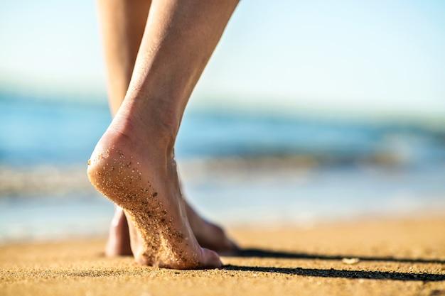 Закройте ноги женщины, ходьба босиком на песке, оставляя следы на золотой пляж. отпуск, путешествия и концепция свободы. люди отдыхают летом.