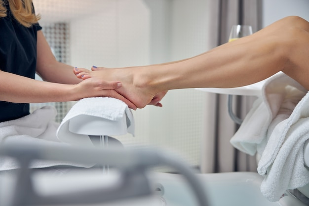 Крупным планом ноги женщины обрабатываются руками профессионала красоты после процедур гигиены