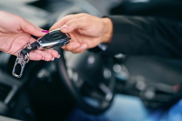 車の男に車のキーを与える女性のクローズアップ。手にセレクティブフォーカス。