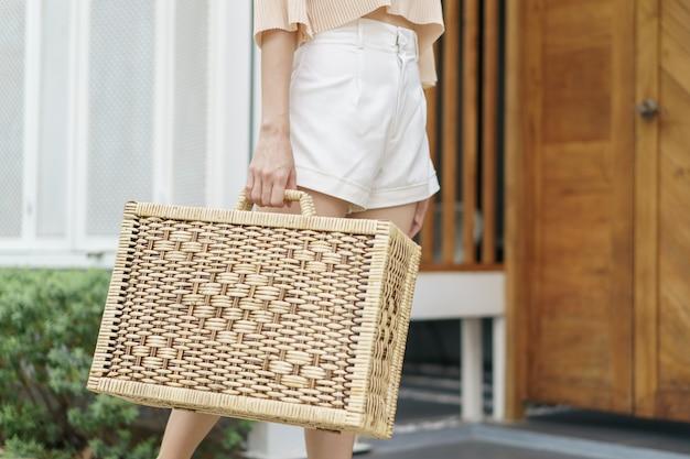 女性の手のクローズアップは、籐のスーツケースを運ぶ。