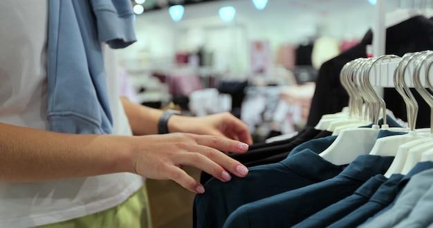 店で節約の若いと割引tシャツの服を選ぶ女性の手のクローズアップ。