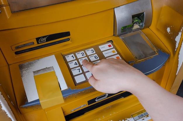 Закройте руки женщины, введя код пароля на клавиатуре банкомата банка