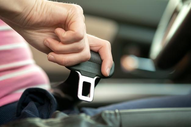 安全のために車の中に座って道路を運転する前にシートベルトを締めている女性の手のクローズアップ。安全な運転と安全な乗馬をする女性ドライバー。