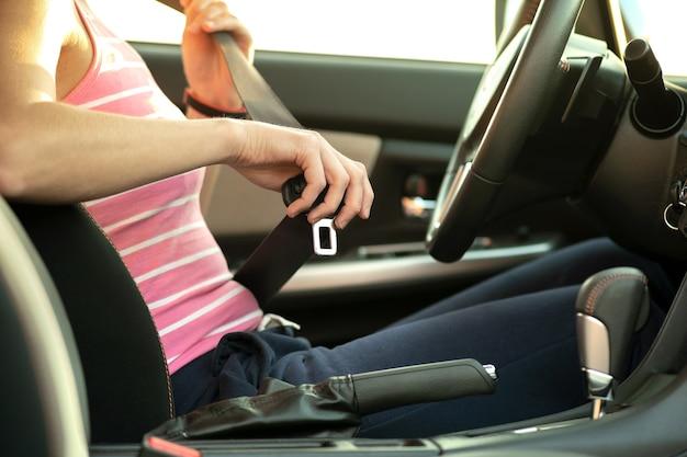 道路を運転する前に安全のために車の中に座っている間、シートベルトを締めている女性の手のクローズアップ