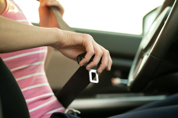 安全のために車の中に座っている間、シートベルトを締めている女性の手のクローズアップ