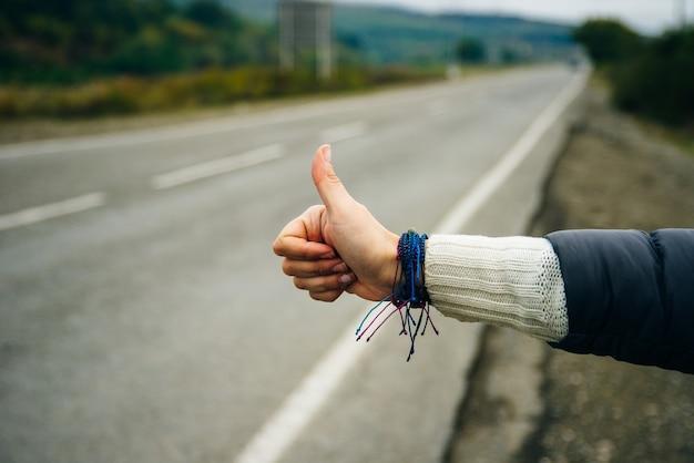 道路でヒッチハイクする女性の手のクローズアップ