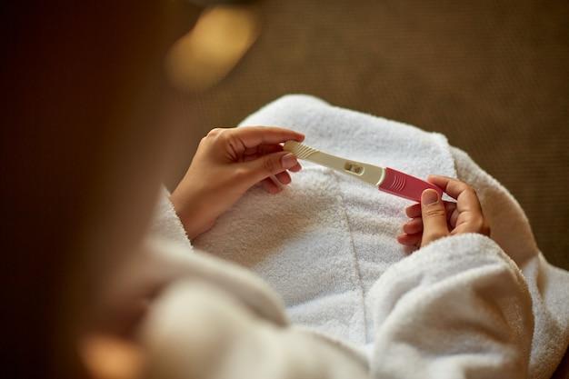陽性の妊娠検査を持つ女性の手のクローズアップ。