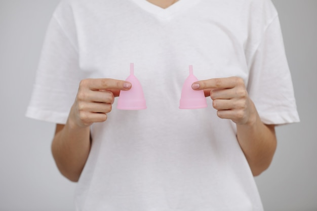 Закройте руки женщина, держа менструальных чаш разного размера,