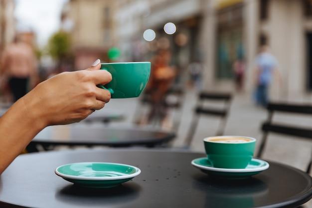 ホットコーヒーの光の青いカップを持つ女性の手のクローズアップ