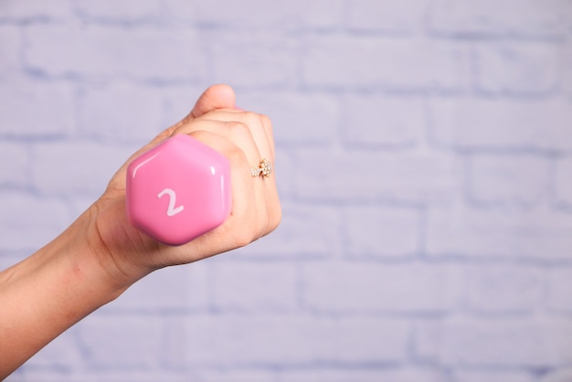 ピンクのダンベルを持っている女性の手のクローズアップ。
