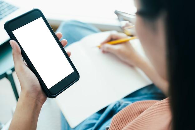 スマートフォンを持つ女性の手のクローズアップ。グラフィックディスプレイモンタージュの空白の画面モックアップ。