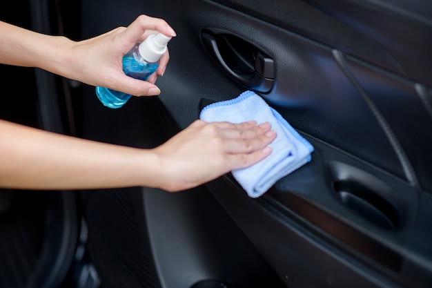Конец вверх руки женщины очищает автомобиль брызгом спирта