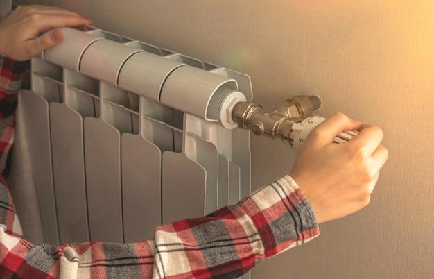 Крупный план руки женщины на термостатическом клапане радиаторного обогревателя на фоне квартиры