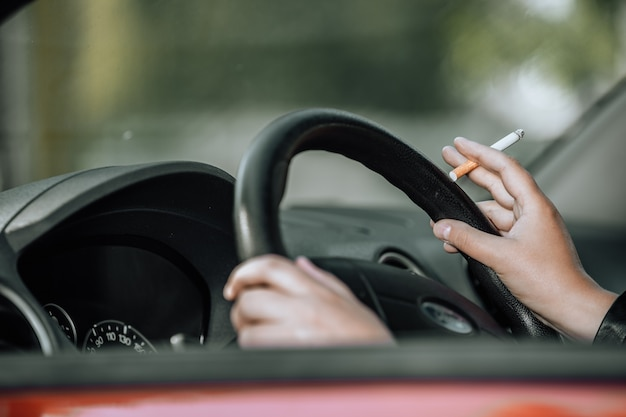 Крупным планом женщина курит сигарету в машине во время вождения автомобиля