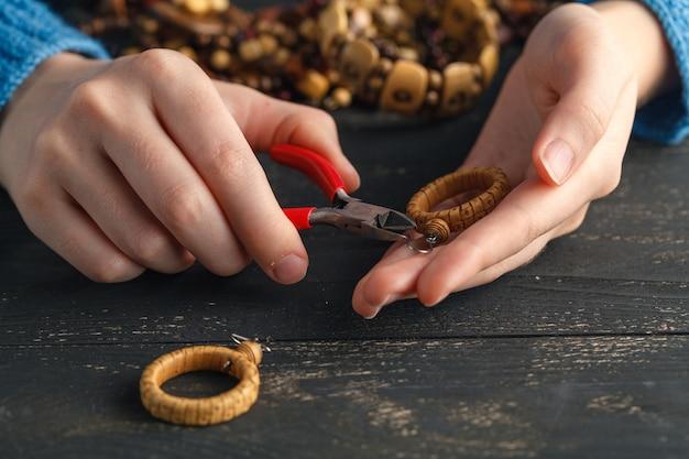 Крупным планом руки женщины нанизывая бисер на шнурке, чтобы сделать художественный браслет из бисера