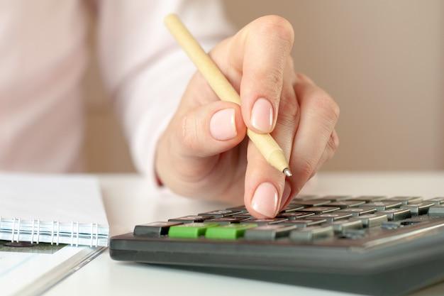 電卓を数えてノートにメモを取ることで女性の手のクローズアップ。財政、経済、技術および人々の概念。セレクティブフォーカス。