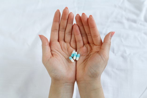 多くの薬と一緒に女性の手のクローズアップ。過剰摂取の概念を取る