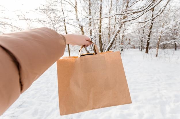 겨울 배경에 테이크 아웃 음식에 대 한 종이 봉지와 여자 손 클로즈업. 고객에게 24 시간 날씨에 관계없이 음식을 배달합니다.