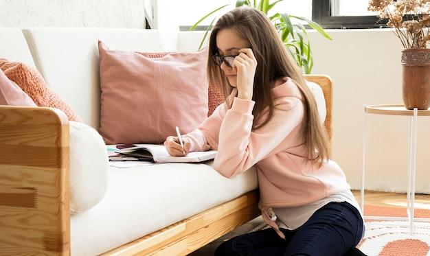 여자 손 쓰기의 클로즈업 또는 집에서 소파에 문서에 서명합니다.