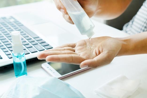 女性の手のクローズアップは、オフィスのテーブルに彼女の手に消毒剤を適用します。感染性ウイルス、細菌、細菌の概念に対する保護