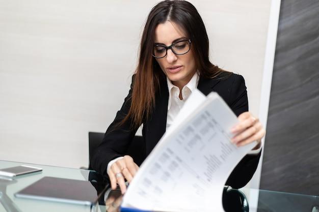 ガラスの机で事務処理をしている女性の手のクローズアップ。秘書のコンセプト