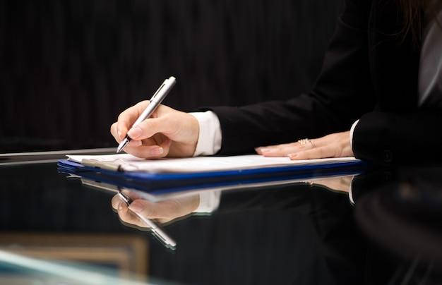 유리 책상에서 서류를 하 고 여자 손의 닫습니다. 장관 개념