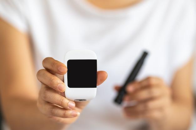 Закройте руки женщины держа и показывая пустой экран измеритель глюкозы и ланцет.