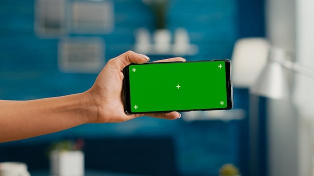 수평 모의 녹색 화면 크로마 키 스마트폰을 들고 있는 여성의 손을 닫습니다. 사무실 책상에 앉아 소셜 네트워크를 검색하기 위해 격리된 전화를 사용하는 비즈니스 여성