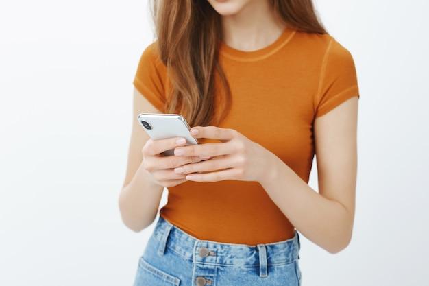 携帯電話、テキストメッセージ、またはアプリケーションのスクロールを保持している女性の手のクローズアップ