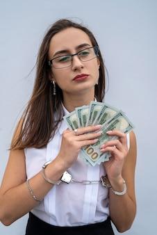 달러를 들고 수 갑에 여자 손의 클로즈업입니다. 뇌물과 부패