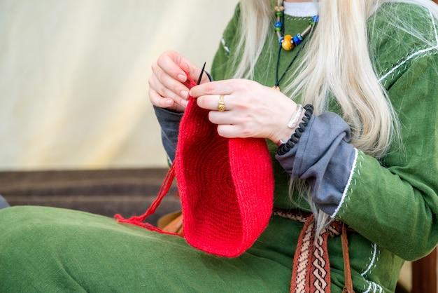 田舎のリネンの服を着て、赤いウールの帽子を編んでいる女性の手のクローズアップ。
