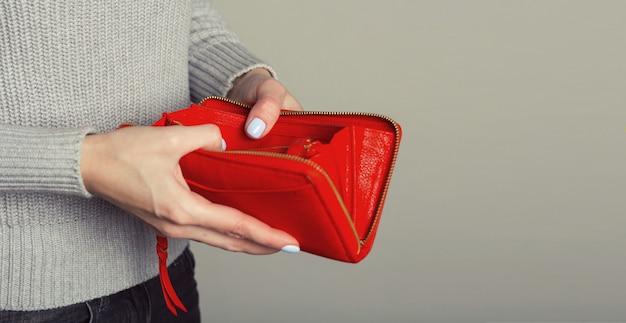 女性の手のクローズアップは、空の財布を開きます。