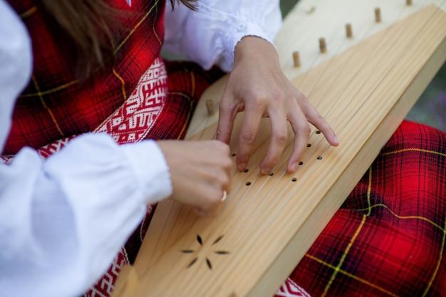 Крупный план женских рук, играющих на струнах арфы