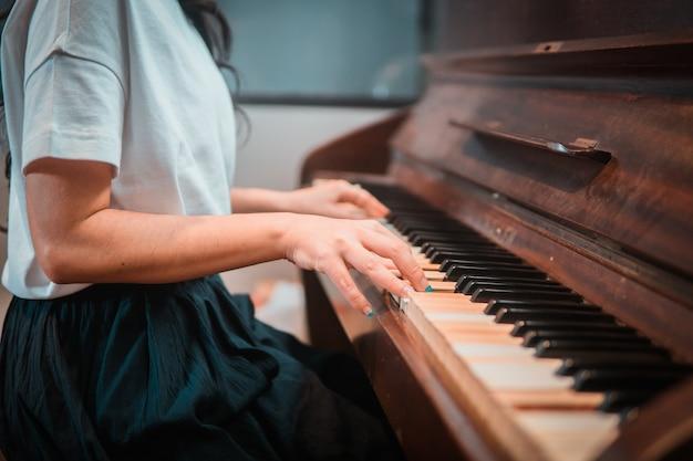 Закройте руки женщины, играя на пианино