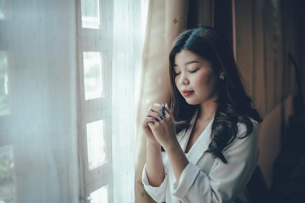 教会で祈る女性の手のクローズアップ。