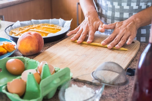집에서 부모와 친구를위한 건강하지만 맛있는 음식을 위해 farina 파스타 복숭아와 계란과 물과 같은 신선한 원료 재료로 케이크를 준비하는 여자 손을 가까이-부엌에서 일하십시오