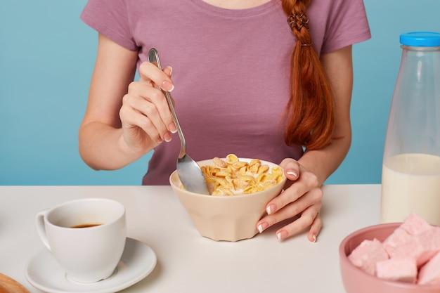 Закройте руки женщины, сидящей за столом, собираясь завтракать