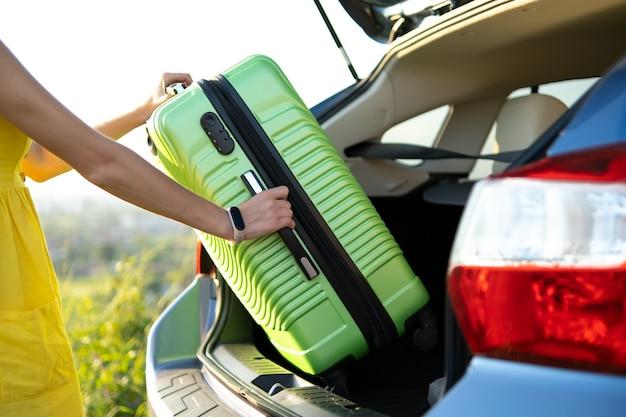 자동차 트렁크에서 녹색 가방을 들고 여자 손을 닫습니다. 여행 및 휴가 개념입니다.