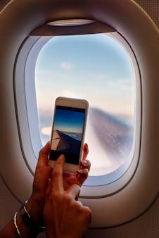 飛行機で写真を撮る女性の手のクローズアップ。旅行のコンセプト。