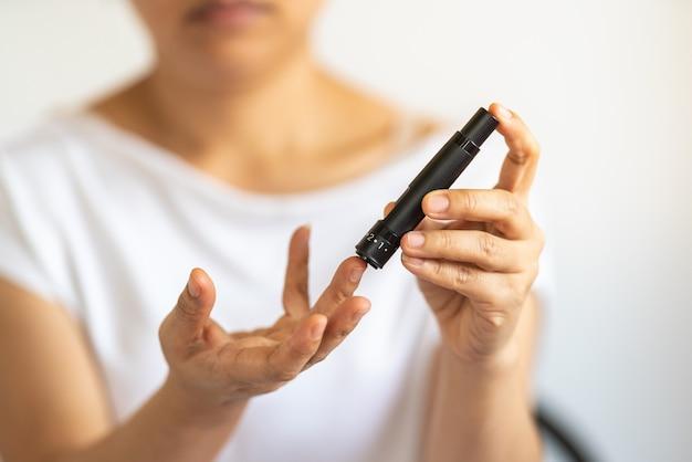 Закройте руки женщины, используя ланцет на пальце, чтобы проверить уровень сахара в крови с помощью глюкометра. используйте как понятие медицины, диабета, гликемии, здравоохранения и людей.