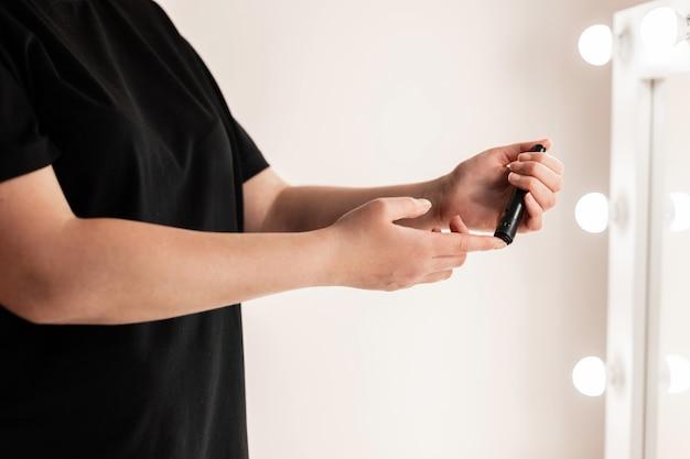 Закройте руки женщины, используя ланцет на пальце, чтобы проверить уровень сахара в крови с помощью глюкометра, используя в качестве концепции медицины, диабета, гликемии, здравоохранения и людей.