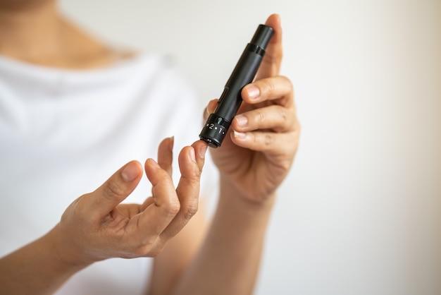 Закройте руки женщины, используя ланцет на пальце, чтобы проверить уровень сахара в крови