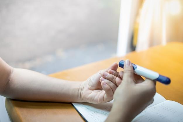 Закройте вверх рук женщины используя ланцет на пальце для того чтобы проверить уровень сахара в крови диабета.